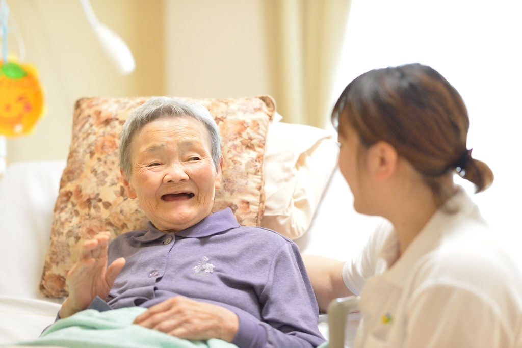 高齢女性を介護する介護士